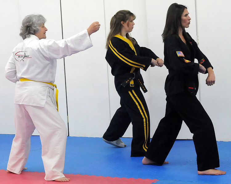 Eileen Van Baren, left, works on technique with instructors Paula Grzenia and Michelle White during an American Kenpo karate class Thursday at International Black Belt Academy, 304 E. 5th St. in downtown Loveland.