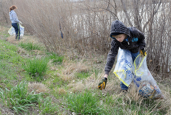 Tyler Benke, 15, reaches for a piece of trash at Jayhawker Ponds while volunteering for the annual spring cleanup with with Tylynn Zeigler, 17, left, and other Thompson Valley High School students on Saturday morning.