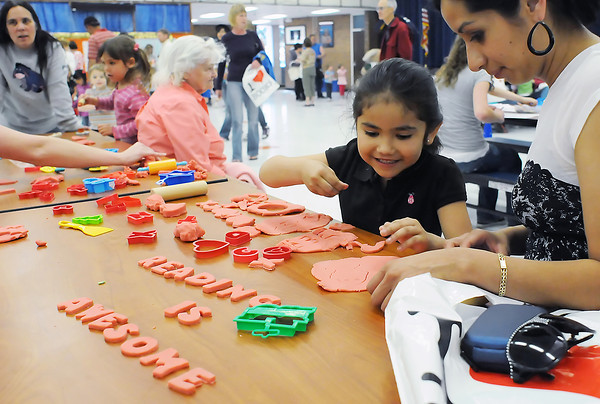 Laura Alba, right, helps her daughter, Jocelyn Gutierrez, 5, as she make shapes and letters out of clay Tuesday at Conrad Ball Middle School during the Reading is Fun Family night event.