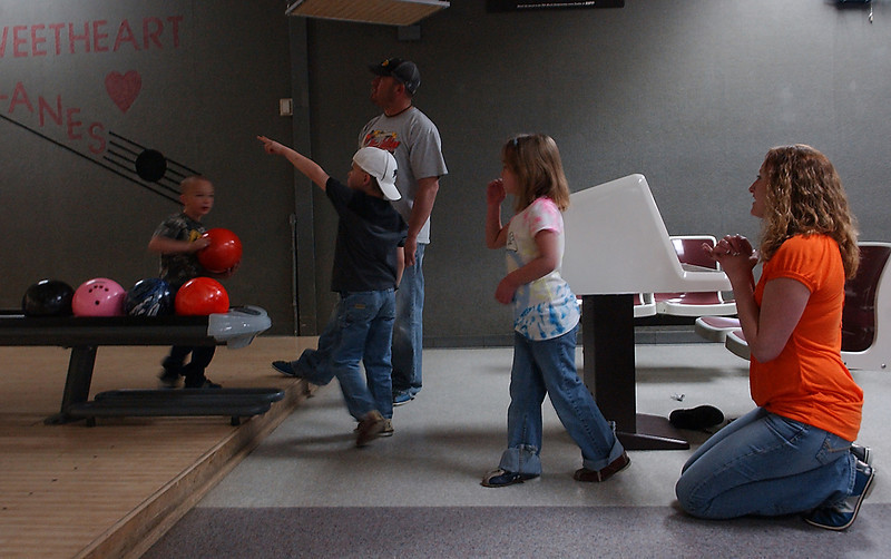 Brandy Smith, right, waits for her daughter, Austin Acres, center right, to bowl at her own benefit.  The group congregated at Sweetheart Lanes, Sunday, with friends and family to support and celebrate Acres' recent heart transplant.  From left to right, Kash Anderson, 5, Kainen Smith, 6, and J.D. Hernandez.