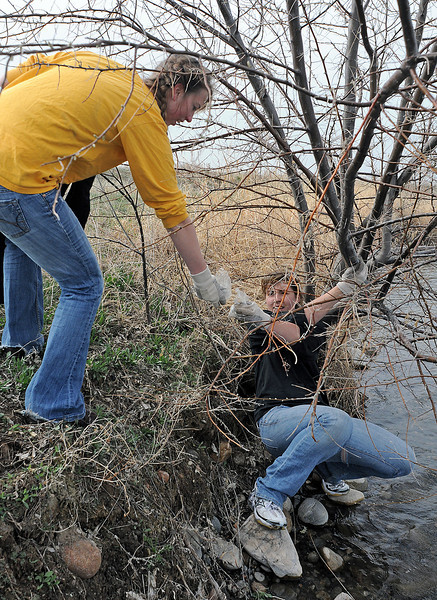 Kristen Adlhock, 18, right, holds onto a tree branch at Jayhawker Ponds as she hands a piece of trash to Mariah Barnes, 17, while volunteering with others during the annual spring cleanup.