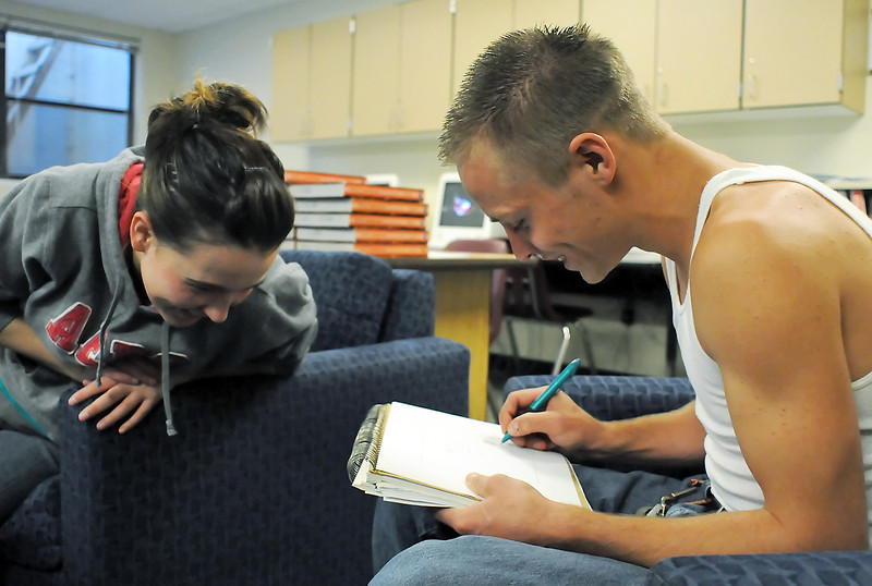 "Ferguson High School student Zach Williams, right, draws a character from the heroic epic poem, ""Beowolf,"" while classmate Brittany Schaeffer looks on during British Literature class Wednesday."