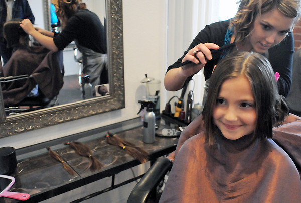 "Seven-year-old Jillian Bohl of Phillipsburg, Kan. has her hair cut by stylist Darby Brown on Friday at Loveland Hair Gallery, 446 N. Garfield Ave., in downtown Loveland. Jillian, who is in town visiting her grandparents, had about 12-14 inches in length cut off, seen at left on the counter, that she intends to doante to Locks of Love. According to the Web site,  <a href=""http://www.locksoflove.org"">http://www.locksoflove.org</a>, the organization ""provides hairpieces to financially disadvantaged children in the United States and Canada under age 21 suffering from long-term medical hair loss from any diagnosis."""