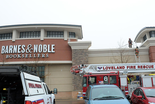 Loveland Fire and Rescue personnel descend from the roof of Barnes and Noble Booksellers, 5835 Sky Pond Ave. at the Promenade Shops at Centerra on Friday. A structure fire report at the bookstore turned out to be a malfunctioning rooftop ventilation unit. Employees and patrons evacuated the store, spending time in the rain while firefighters from Loveland Fire and Rescue Station 6 checked out the trouble.