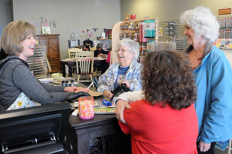Artsy Stamps and Paper Crafts co-owner Dianna Boehner, left, shares a laugh with Peggy Stroh, middle, Peachie Pherson, right, and Roxanne Infante while ringing up their purchases Wednesday at the store.