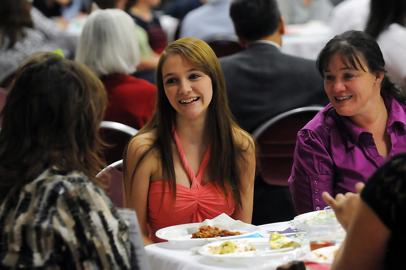 Mountain View High School junior Elissa Stone, 17, center, and her mother, Kristal Boyd, right, chat with Laura Ulmer, left, during the Heroes Among Us event Wednesday at Immanuel Lutheran Church where Elissa read her nomination story to those in attendance about why Ulmer is her hero.