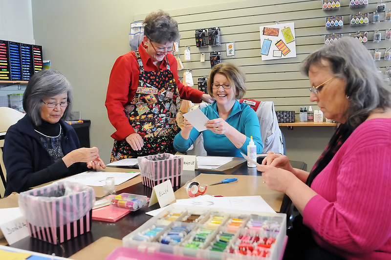 Artsy Stamps and Paper Crafts co-owner Patsy Kral, standing, assists students during an embroidery-on-cards class Wednesday at the new business' location at 4880 Thompson Parkway east of Loveland. Seated from left are Joan Takamine of Greeley and Loveland residents Michaele Gillette and Ellyn Knowlton.