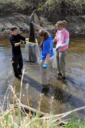 Jacob Whitler, 13, left, holds a trash bag for his sister, Amanda, 15, while volunteering along with their mother, Lisa, for the City of Loveland's Annual Waterway Cleanup in Chubbuck Ditch.