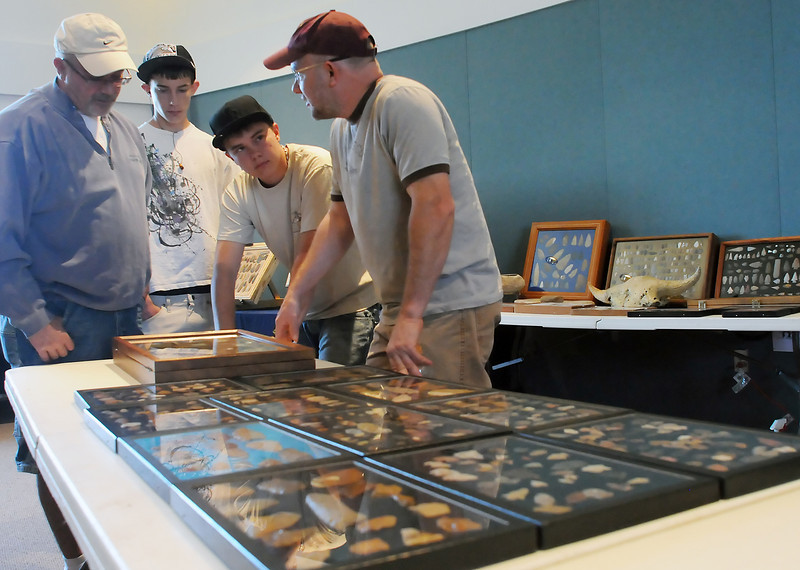 Berthoud residents Rick Wilson, left, and his sons, Kaleb, 15, and David, 16, chat with Shane Skutdik of Denver while looking at arrowheads on display Saturday at Poudre Valley REA during the Loveland Archaeological Society's annual Spring Into Archaeology show.