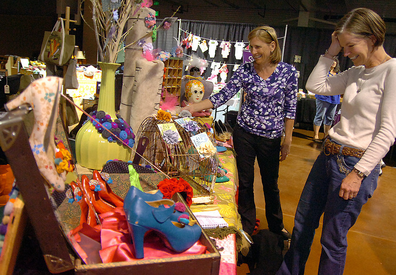 Lindsay Cantley, left, and Kathy Boeding get a closer look at some items for sale at the Fern and Sprout booth during Operation Re-Scrap at The Ranch in Loveland. Photo by Jenny Sparks