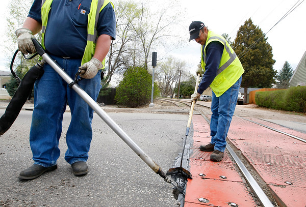 Scott Muirhead shoots tar into cracks while Brad Nazarenus smooths it out on Cleveland Avenue between East 10th and 11th Streets. The City of Loveland Streets Division works from November to April to repair cracks in the cities streets. (Photo by Gabriel Christus)