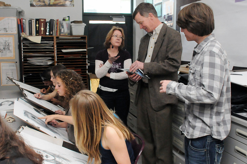 Mountain View High School senior Christopher Stone, right, looks on while Gov. John Hickenlooper chats with art teacher Anne McManus while visiting her drawing class during a tour of the school Friday afternoon.