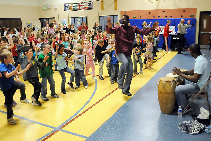 Maputo Mensah, center, leads Sarah Milner Elementary School students and teachers in an African dance while Mawuenyega Mensah plays drums during a multi-cultural assembly in the school's gymnasium Wednesday.
