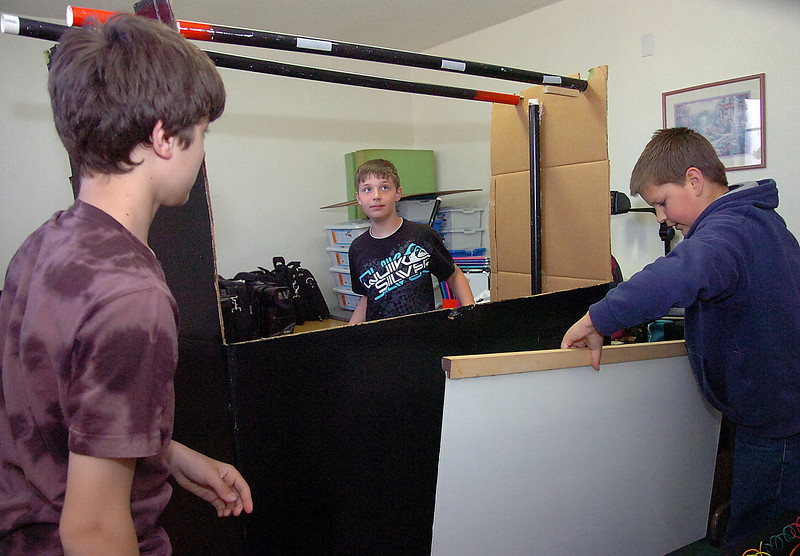 Dakota Jager, 13, left, Josh Zachman, 12, center, and Benjamin Flanscha, 12, set up the stage for their puppet show Thursday.