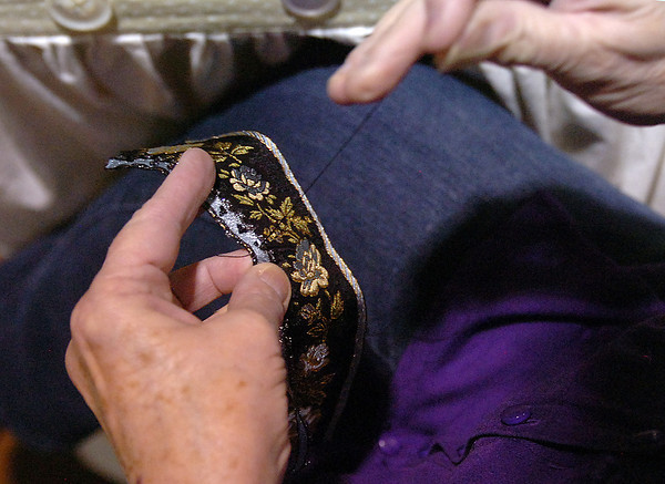Kathleen Sigg sews beads onto a french jacquard Friday at her booth, Traditions,  during Operation Re-Scrap at The Ranch.