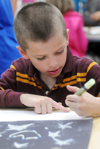 "Monroe Elementary School first grader Logan Kenyon, 7, draws a constellation that he named ""The Heart"" on Friday during Science Night at the school."
