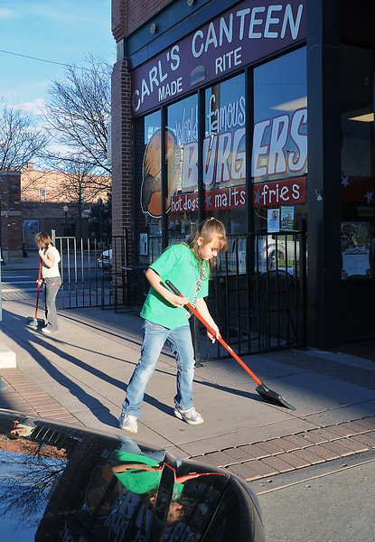 Eight-year-old Nicole Stepina, right, and her sister, Mandy, 6, work together Tuesday afternoon sweeping in front of their great-grandmother Mary Aguilar's restaurant located at Fourth Street and Lincoln Avenue in downtown Loveland. Aguilar said the girls were working to save up money for a family trip later in the year to go to Sea World in San Antonio.