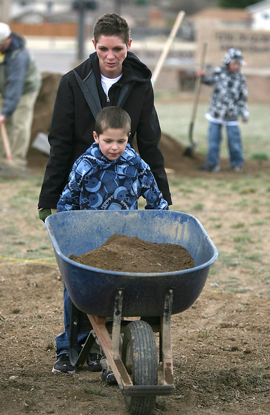 Kimberly Culp helps her son, Thomas, 6, take a wheelbarrow full of soil to fill a planter box in the King of Glory Lutheran Church community garden Sunday at 29th and Wilson. (Photo by Gabriel Christus)