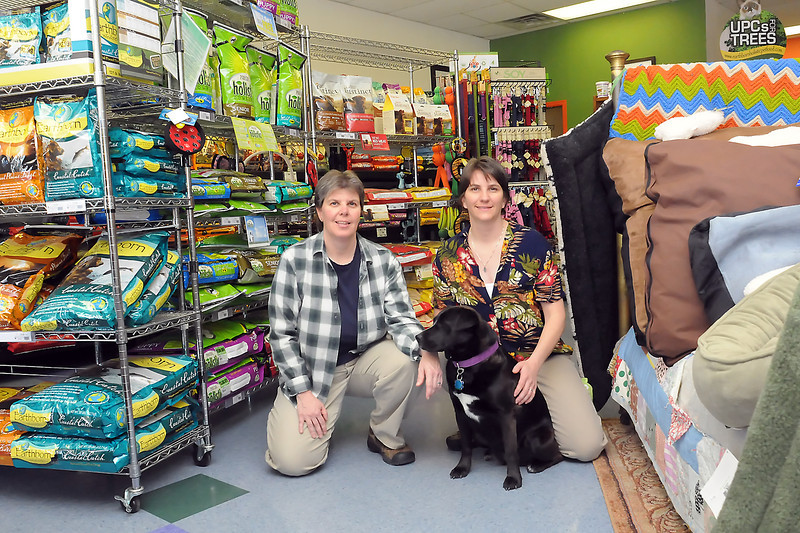 Hank's Pet Food Market co-owners Lisa Sauer, left, and Teresa DeBuelle pose Wednesday with their dog, Abby, in their store located at 2255 W. Eisenhower Blvd. in Loveland.
