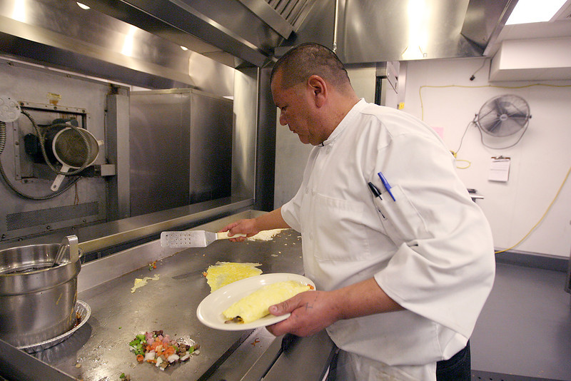 Head cook Chuck Orona,  , prepares a veggie omelet for a customer Saturday at Johnson's Corner. The veggie omelet is one of the few items on the menu that comes with tomatoes due to a shortage of produce out of California. (Photo by Gabriel Christus)