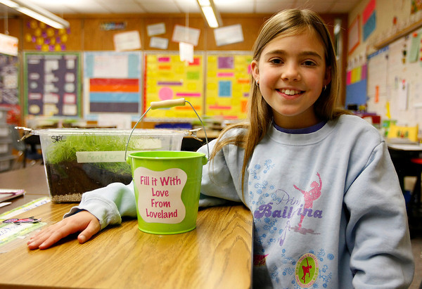 Allison Fleischersits in her classroom at with a bucket to collect money to send to Red Cross for the Japan tsunami relief effort on Monday at VanBuren Elementary School. Fleischer collected more than $400, many notes of encouragement and 2 pieces of oragami. (Photo by Gabriel Christus)