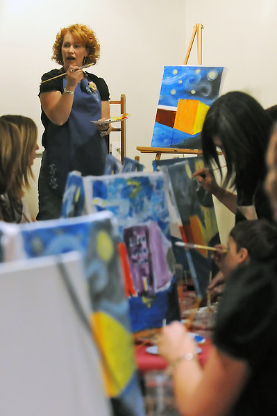 Studio Vino artertainer Tracie Jenkins, back, leads participants in a painting class Thursday evening during a friends and family event in downtown Loveland at 426 N. Lincoln Ave.
