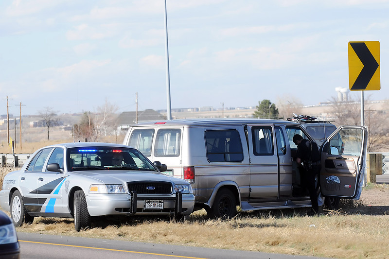 Law enforcement personnel work the scene of a motor-vehicle accident Friday, April 1, 2011 in the median between lanes of Interstate 25 at Highway 402.