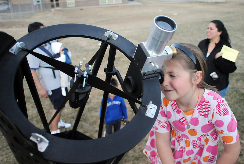 Eight-year-old Carrie Kingston peers at the moon through a 12 1/2-inch reflecting telescope outside Monroe Elementary School during Science Night on Friday.