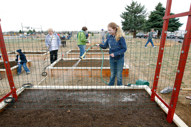 Meghan Morris, 12, waters the dirt, preparing it to plant seeds Sunday at King of Glory Lutheran Church. (Photo by Gabriel Christus)