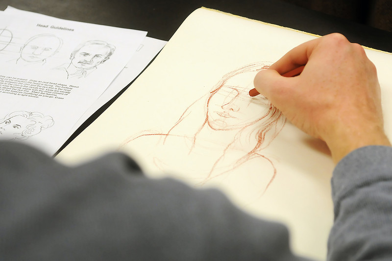 Fort Collins resident Jason Reid uses a conte crayon to sketch a live model Friday during a sample class at Aims Community College in downtown Loveland as part of the school's free college day event.