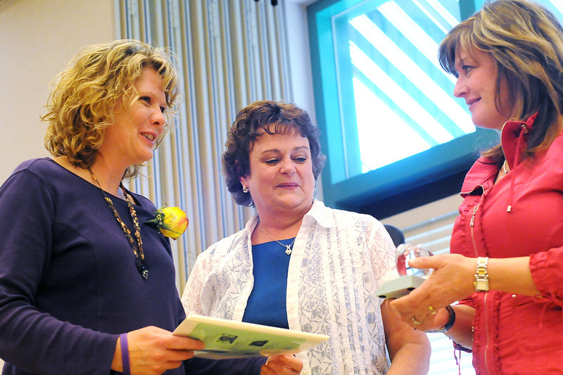 Ivy Stockwell Elementary School teacher Linda Pickert, left, accepts her Crystal Apple award from Thompson Education Association president Laurie Shearer, middle, and Susan Krantz of Horace Mann Insurance Companies during the 10th Annual Crystal Apple Awards on Friday at the Chilson Senior Center.