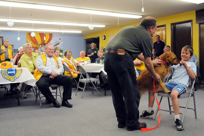 Eight-year-old Colby Bilson, right, assists International Hearing Dog field representative Bob Cooley as he and his hearing dog, Cami, perform a demonstration Thursday evening at Faith Evangelical Church, 2707 N. Wilson Ave., during a joint meeting of the Loveland Sundown Lions Club and Berthoud Lions Club. Cooley said that the hearing dogs are trained to alert their deaf owners to sounds like doorbells, phones or smoke alarms as well as other sounds. He said the dogs also provide companionship and security.