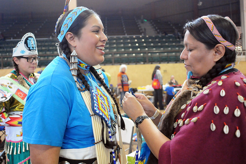 A.J. No Braid, left, and her daughters Larissa, 17, middle, and Lara, 13, get ready to participate in the grand entry Sunday during the Spring Contest Powwow and Indian Art Show at the B.W. Pickett Equine Center in Fort Collins.