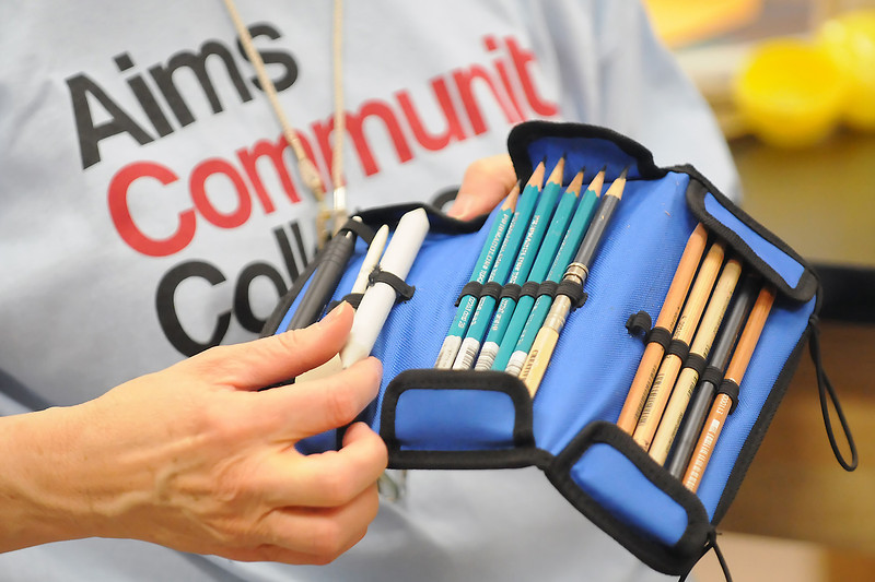 Aims Community College art instructor Victoria Lisi shows students the various drawing tools she uses during a sample drawing class Friday for the school's free college day event.