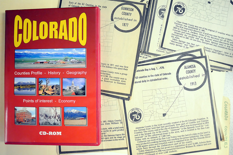 A copy of Octavio Nado's educational CD-ROM on the counties of Colorado sits atop newspaper clippings that were the inspiration for the project to document all 64 Colorado counties.