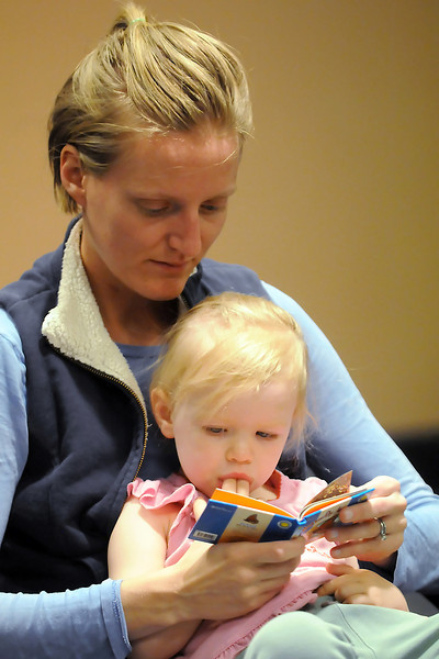 Alyson Wiedenheft and her daughter, Lexie, 2, read along with a tiny book about butterflies during a meeting of the Wee Read program on Wednesday at the Loveland Public Library.