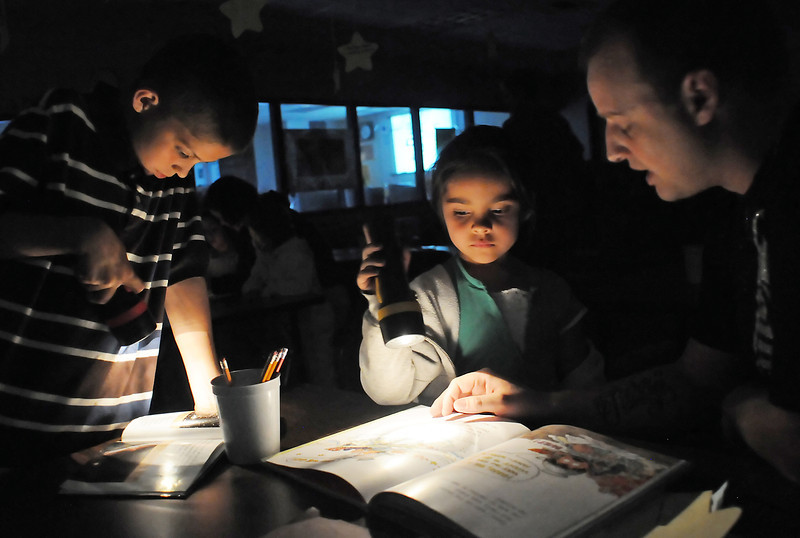 Monroe Elementary School third grader Miguel Deollos, 9, left, his sister, Solana Vasquez, 6, a kindergartner at the school, and their uncle, David Province use flashlights to illuminate the pages as they read together during a Reading Under the Stars activity at the school Friday for Science Night.