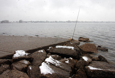 A fisherman waits in his warm car with his pole in the water as snow covers the rocks on the southeast shore of Lake Loveland Thursday morning.