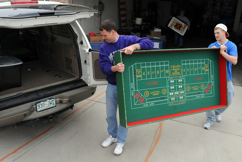 Mountain View High School junior Patrick McQueen, 16, right, and his father, Gordo McQueen, carry a craps table that will be used during the casino-themed Prom-A-Rama event at the Chilson Recreation Center for area high school students.