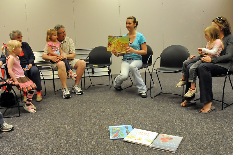 Emilee Mai, 15, center, holds up a book to show the picture as she reads to a group during the Wee Read program on Wednesday at the Loveland Public Library. From left are Lacey Berg, 3, Margaret Hood, Marley Mitchell, 3, John Mitchell, Mai, Chamberllin Julian, 5, and Heather Julian.