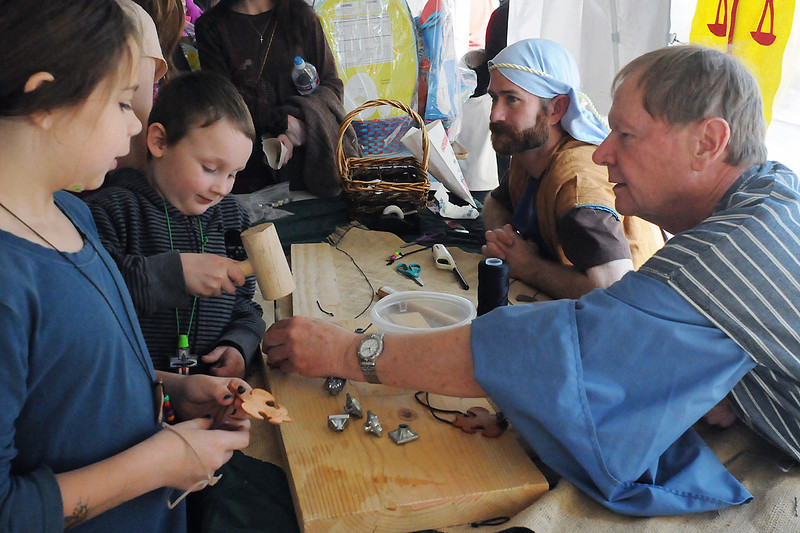 Nine-year-old Christina Vasquez, left, and Gavin McDonough, 5, make leather necklaces with the assistance of Dwight Carlson, right, and Tom Hoffman during the Church of the Nazarene's Ninth Annual Easter Marketplace on Saturday.
