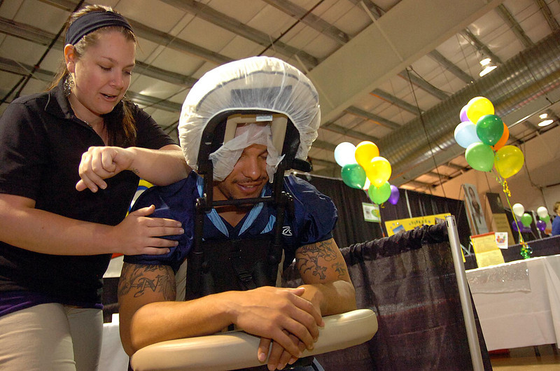 Tara Clarken, lead therapist at Massage Heights, works some knots out of Colorado Ice player Eryk Anders back Wednesday during the Loveland Chamber of Commerce Business Expo at The Ranch in Loveland.