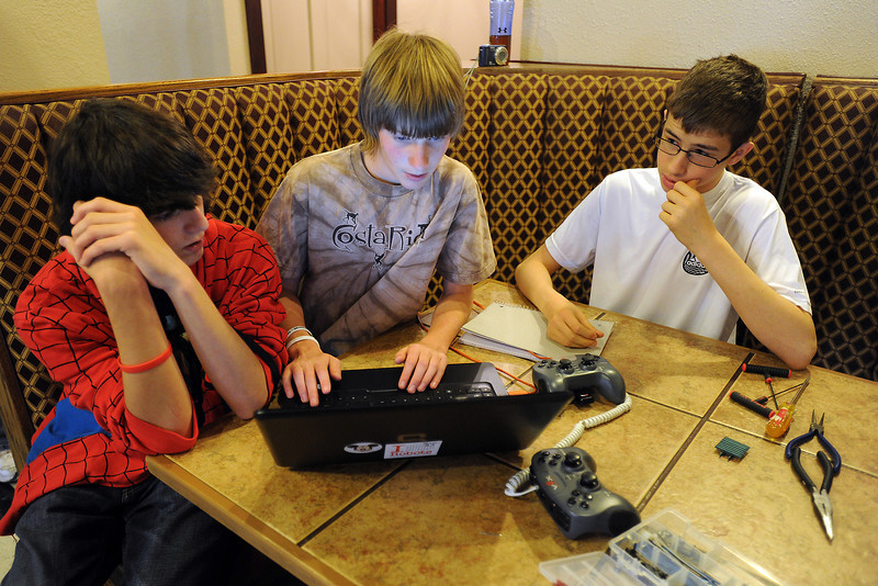 Robotics players from Altona Middle School's Arkham Asylum Members team out of Longmont use a laptop computer to adjust the program that runs their robot during a practice session in downtown Loveland on Saturday, April 7, 2012.