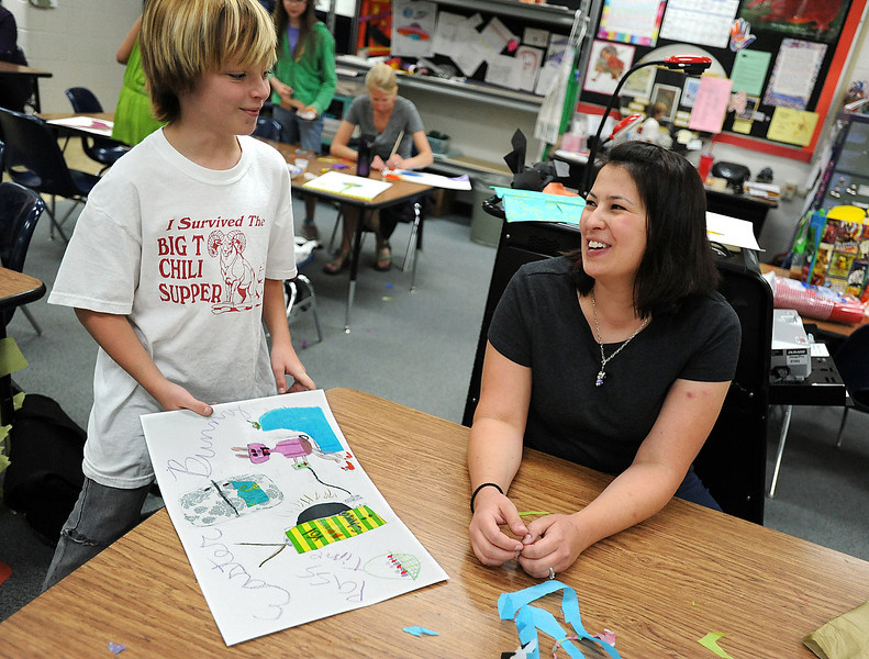 "Loveland artist Kerri Ertman, right, laughs with Big Thompson Elementary School fifth-grader Beau Farago, 11, as he tells her he added a mustache to the ice cream bowl on his collage piece Tuesday during the Thompson School District Shadows in the Arts program at Namaqua Elementary School. She told Beau ""When all else fails put a mustache on ice cream!"""