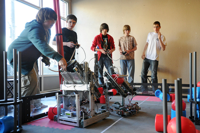 Robotics team players, from left, Mark Stewart, 14, Chase Rayment, 14, Arman Long, 14, Rhett Sandal, 14, and Trey Gallagher, 13, compete in a scrimmage on a practice field set up in downtown Loveland at 210 E. Fourth St. on Saturday, April 7, 2012.