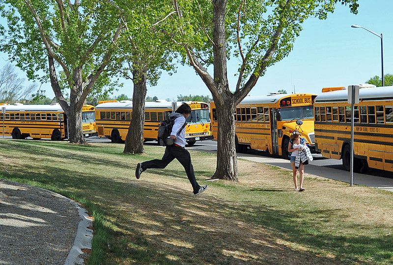 A Thompson Valley High School student sprints to catch his bus Monday after school in Loveland.