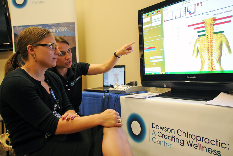 Fort Collins resident Allison Humphries, left, chats with Dr. Aspen Dawson about the results of a check she had done of her nervous system at the Dawson Chiropractic: A Creating Wellness Center booth during the Loveland Community Health Fair at the McKee Conference Center on Saturday, April 14, 2012.