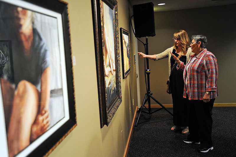 Fort Collins resident Elizabeth Fuller, back, and Anita Chacon of Loveland look at Loveland Rotary Clubs Scholarship Winners' paintings on display at the Loveland Museum/Gallery during the Governor's Invitational Art Show and Sale on Saturday, April 28, 2012.