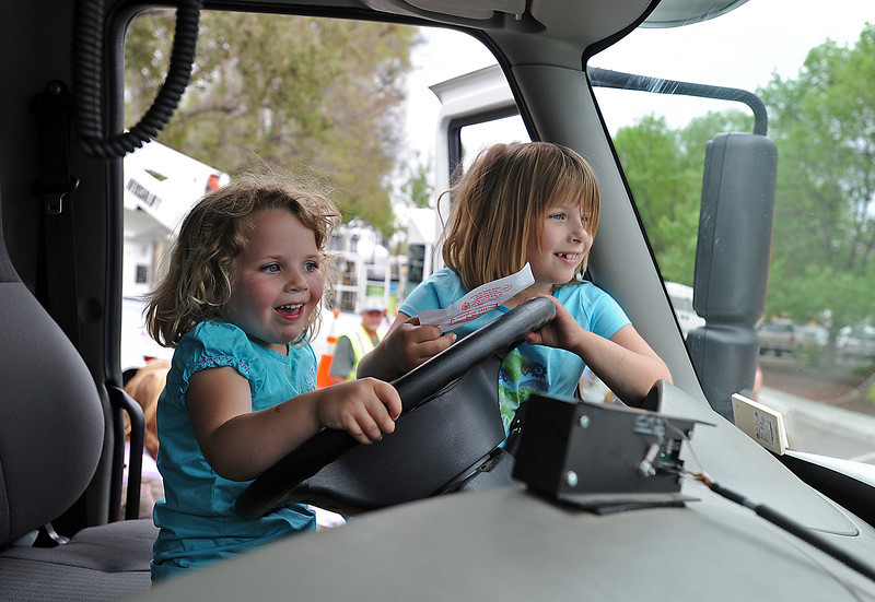 Amy Bullett, 4, left, and Sarah Bullett, 6, have fun behind the wheel of a snow plow during Children's Day.