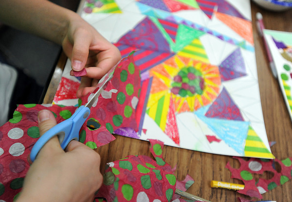 Mikayla Pennock, 11, a Coyote Ridge fifth-grader, cuts pieces of tissue paper while creating a collage Tuesday during the school district's Shadows in the Arts program at Namaqua Elementary school in Loveland.